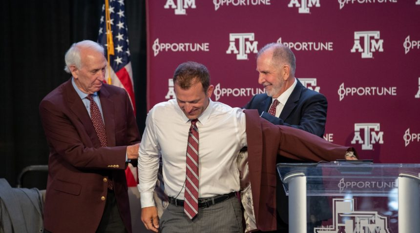 Texas A&M Interim Director of Athletics R.C. Slocum (left) and President Michael K. Young gift a maroon jacket to incoming Director of Athletics Ross Bjork.