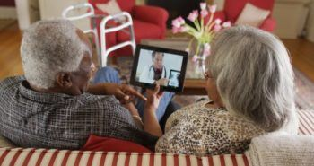 Elderly couple watches an iPad that features a doctor reviewing an x-ray