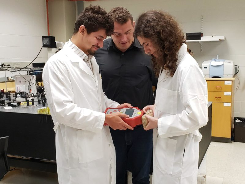 Mark Krimmer, an undergraduate student (left), Dmitry Kurouski (center) and Charles Farber, a graduate student (right) demonstrate how to scan grain for nutrient content with a handheld Raman spectrometer.
