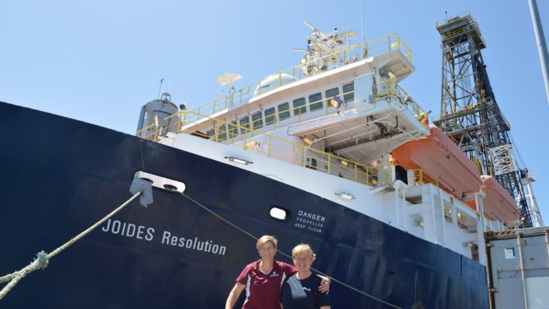 Two woman stand in front of a ship