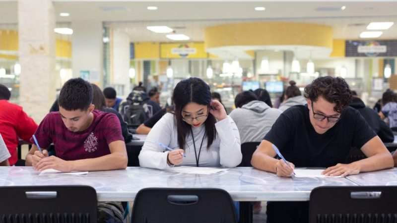 three students look down at papers while sitting at a cafeteria table