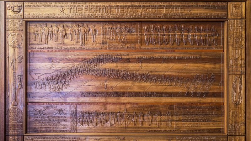 close up view of wood relief sculpture detailing history of aggie band