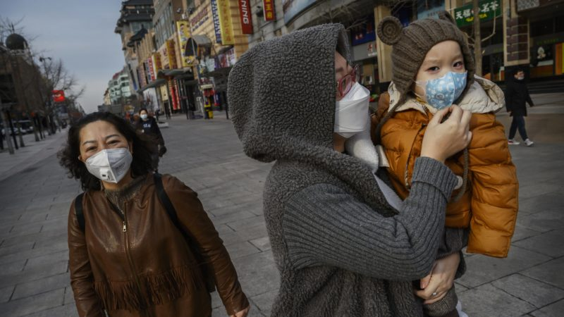 a chinese woman and her child wear protective masks in a nearly empty commercial street in beijing