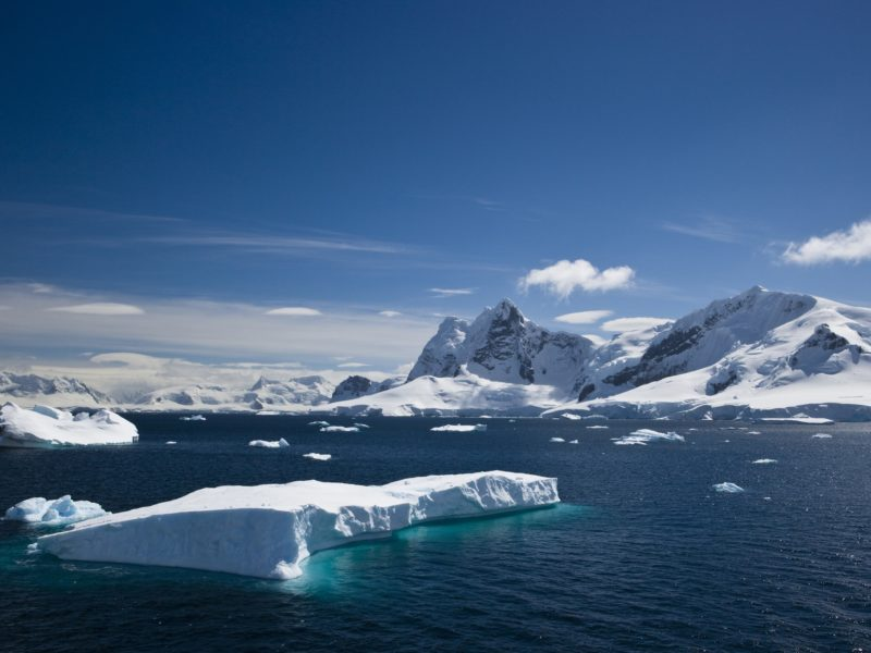 An iceberg floating on the water in antarctica, with snowy mountains in the background