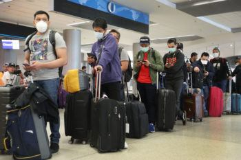 People standing with suitcases and wearing face masks in line at airport