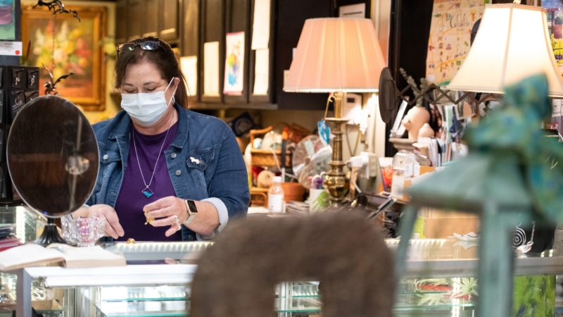 woman wearing a face mask behind counter at antique store