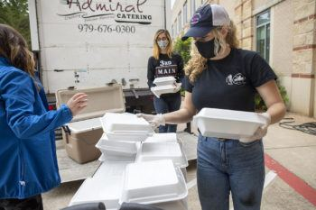 women wearing masks and gloves boxing up food in styrofoam containers