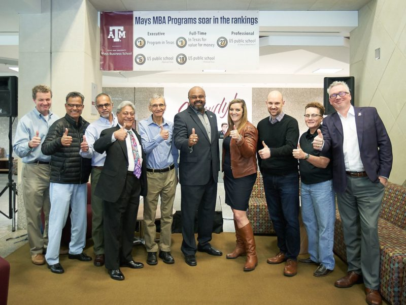 faculty members standing in line giving gig'em sign