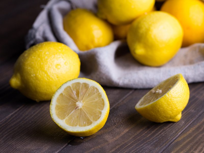 Group of fresh ripe lemon in sackcloth on an old vintage wooden table