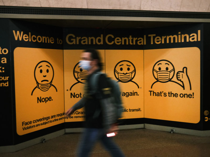 blurred image of man wearing face mask walking by display in grand central terminal displaying how to properly wear a face mask