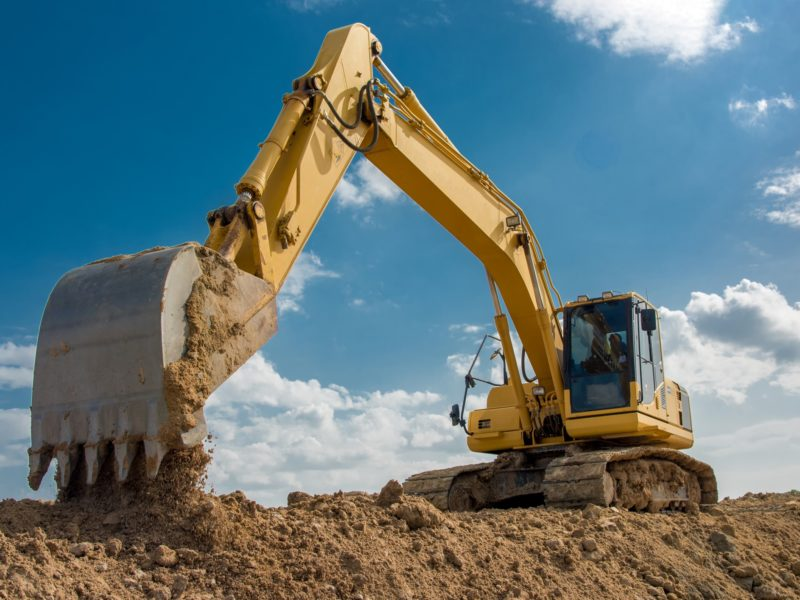 excavator on construction site in front of blue sky