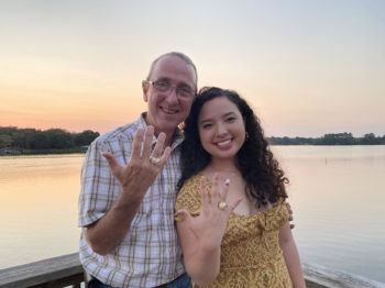 "Kenneth ""Kip"" Martin '86 and his daughter Vivian Martin '21 pose before a lake, showing off their Aggie rings"