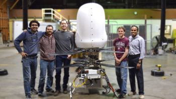 group photo of team standing next to their machine