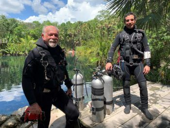 Iliffe and Calderon stand side by side in wet suits with oxygen tanks near the water in a tropical setting