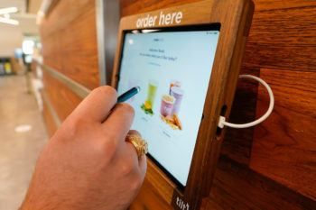 close up of man's hand holding a stylus at self-order dining tablet
