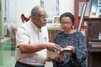 wayne sadberry shows a book to andrea roberts in a museum