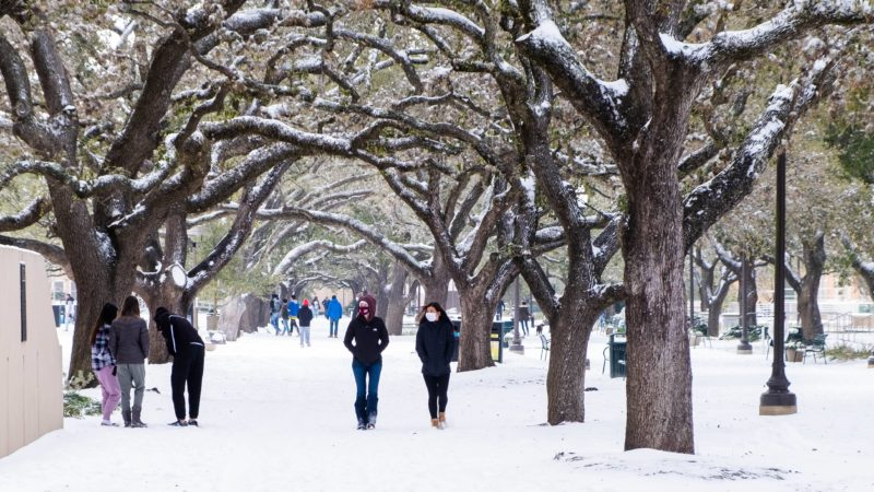 students walk through campus covered in snow