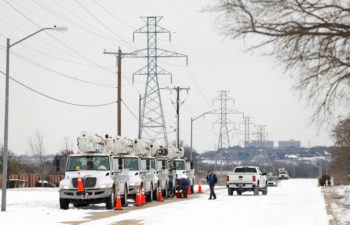 eletric service trucks lined up at power lines in snow