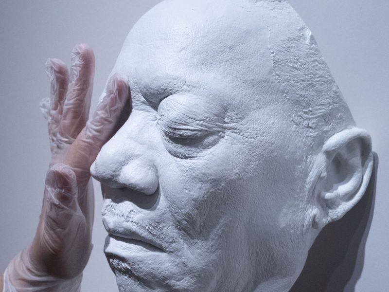 a hand touching a cast resin mask of Bobby Blue Bland