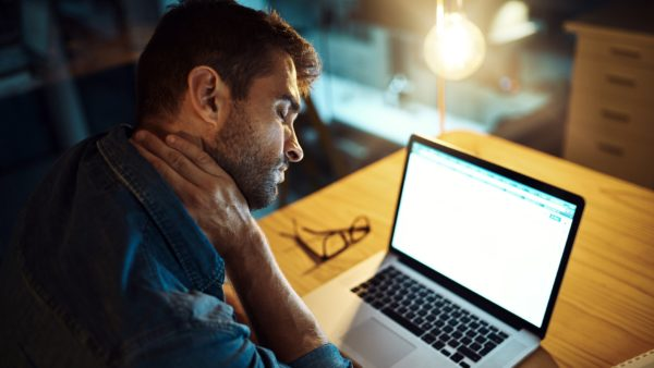 man sitting at a desk with laptop rubbing his neck