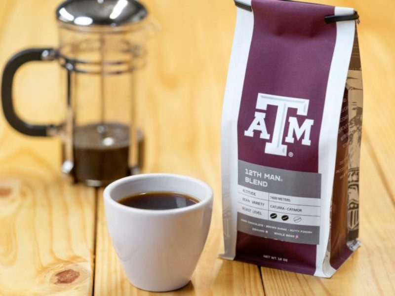 photo of a french press and coffee cup next to a bag of coffee with a&m logo