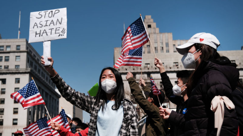 a group of people protest outside, holding american flags and signs tht say