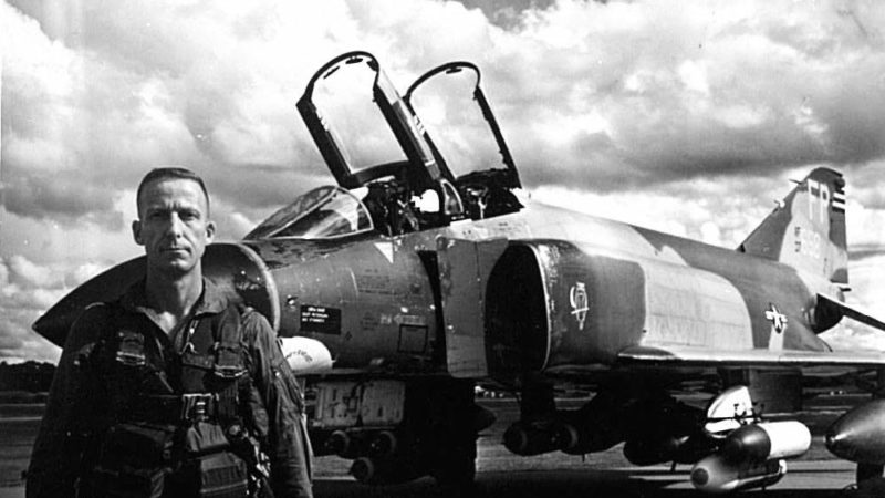 black and white photo of frazier standing next to an airplane