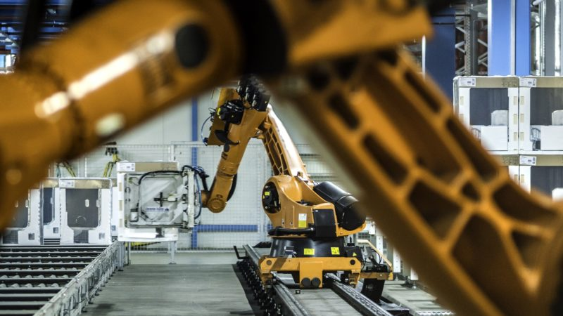 Photo of two orange robotic arms moving washing machines on a factory assembly line.