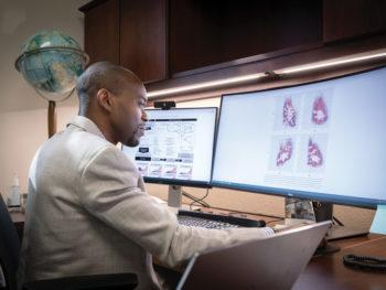 portrait of martial ndeffo in his office sitting in front of two computer monitors