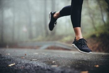 view of a woman's legs running on a road on a foggy day