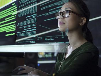 a photo of a woman looking at a computer screen