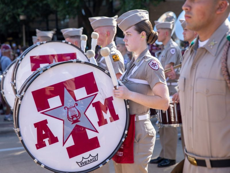 a photo of Amanda Lovitt standing with the Aggie band during Corps March-in